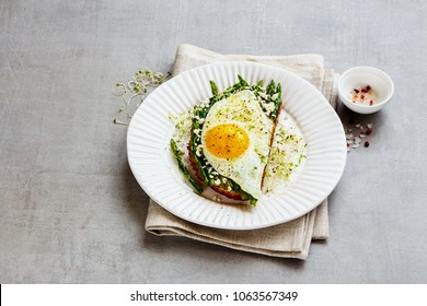 Close up of tasty spring sandwich plate. Green aspargus, fried egg, feta cheese and micro greens over light concrete background. Healthy eating, slimming, diet lifestyle concept. Side view