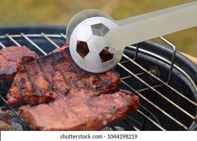 close up of tasty steaks on barbecue grill with Football World Cup tong