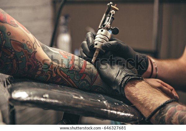 close up tattoo machine. Man creating picture on hand with it in salon