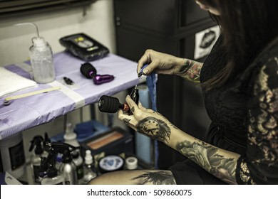 Close up tattooer hands changing tattoo machinery needle in tattoo studio