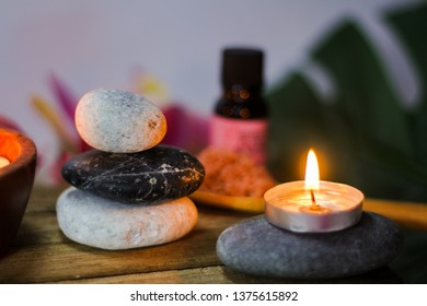 Close up of tea light candle in with other spa elements like zen stones and deep red plumeria flower on wooden board.