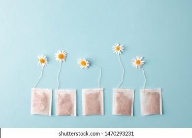 Close up of tea time. Dry camomile tea in the tea bag, minimal concept. Chamomile anti-depression beverage creative lay out
