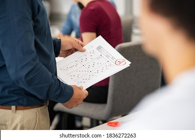 Close up of teacher hands holding test result in high school class. University professor holding answer sheets with grades while distributing them to the college students. Lecturer giving test results