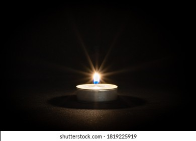 Close up of tealight candle with lens flare