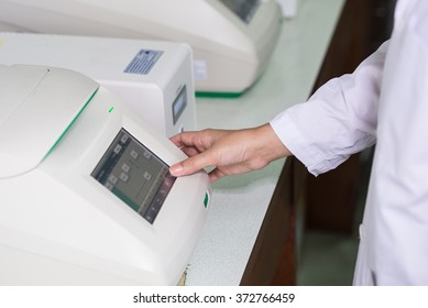 Close up of technician hand entering information on keypad for electronic laboratory device