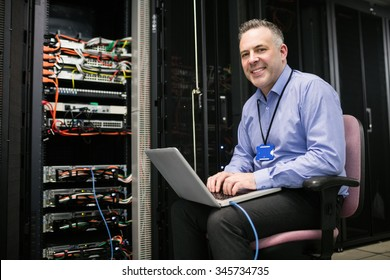Close up of technician using laptop in server room at the data centre