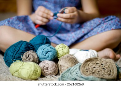 close up of teen girl with crochet hook and yarn