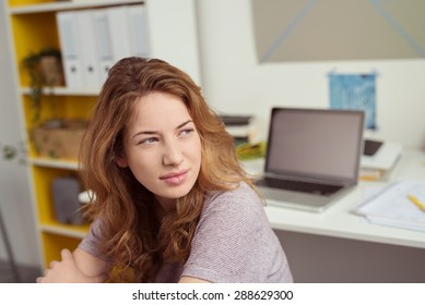 Close up Teen Girl at her Study Area Inside the House, Looking Into Distance in a Pensive Facial Expression.
