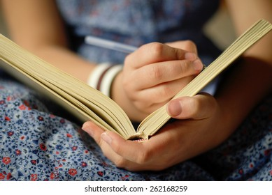 close up of teen girl writing into her notebook