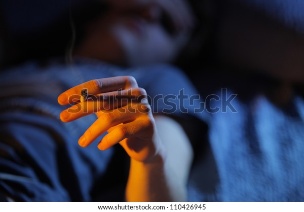 Close up of teenage boy smoking drugs lying on the couch, copy space