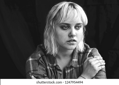 Close up of teenager with depression and bulimia sitting alone in dark room. She covers her face with hands. Mental problems with depression and bulimia. Black and white photo.