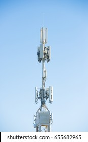 Close up telecommunication tower for cellphone and wireless broadcasting, blue sky as background.