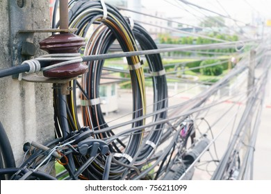 Close up of  telecommunication wires attached to the electric pole, the chaos of cables and wires on an electric pole in Bangkok, Thailand, concept of electricity and telecommunication wiring cables