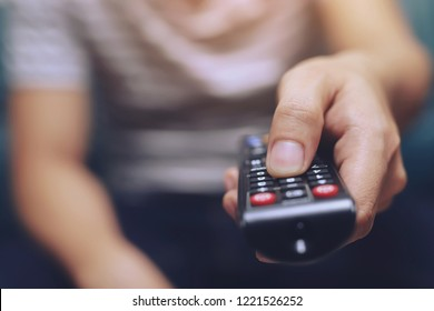 close up Television remote control in casual man hands pointing to tv set and turning it on or off. select channel watching tv on his sofa at home in the living room relax.