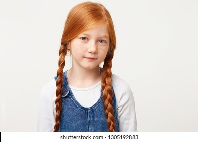 Close up of tender little girl with freckles and braided in two long plaits red hair, stands calmly directly looking camera, dressed in jeans overall isolated on white background