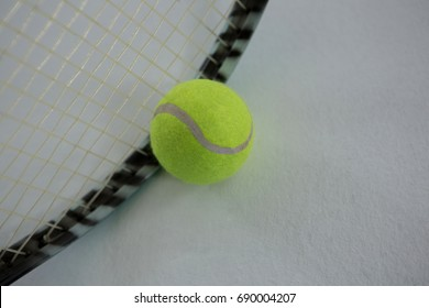Close up of tennis ball by racket against white background