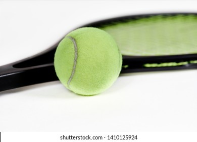 Close up of a tennis ball laying next to a tennis raquet with shallow depth of field