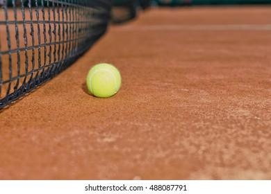 Close up of tennis ball lies near the net on clay court