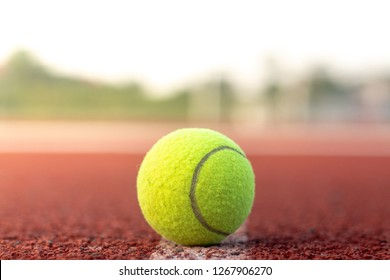 Close up tennis ball on the center of clay court by sport concept.