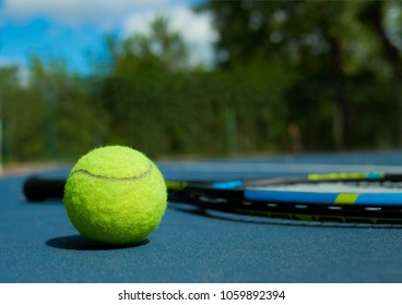 Close up of tennis ball on professional racket background, laying on blue tennis court carpet. Photo of professional sport equipment. Concept of tennis outfit photografing.