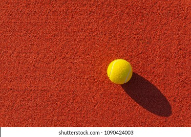 Close up of a tennis ball on a red surface of a clay court.
