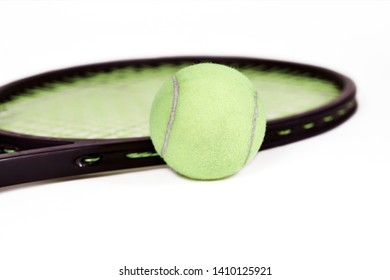 Close up of a tennis ball with a tennis racquet behind it with shallow depth of field