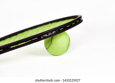 Close up of a tennis racquet laying on top of a tennis ball with shallow depth of field