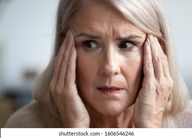 Close up of terrified mature woman look in distance thinking remembering, scared senior female retiree grandmother feel scared frightened, face strong fear or anxiety at home, having panic attack