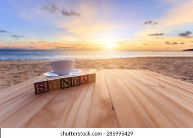 Close up text wood block and coffee cup on wood table at sunset or sunrise beach