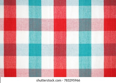 Close up texture of Christmas red and green plaid pattern, checkered fabric of picnic mat in Christmas color gingham background.