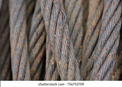 close up texture of rust sling wire, background of old sling in front of a car.