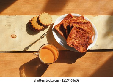 Close up Thai milk tea in glass cup. Brown toast on white plate. Cookies on wooden board background with hard light and shadow in the warm yellow morning. Bekery breakfast time to start new day