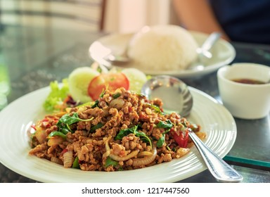 Close up of Thai stir fried pork with basil leaf and chilli on white dish