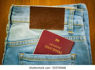 close up Thailand passport inside jeans pocket with brown leather tag on light blue jeans on wood background