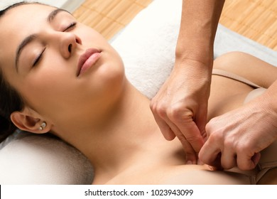 Close up of therapist applying pressure on female patient.Hands massaging chest.