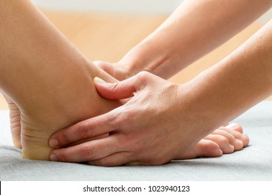Close up of therapist applying pressure with thumbs on female ankle.