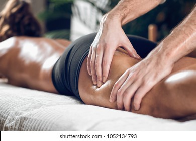 Close up of therapist doing anti cellulite Madero therapy hand massage to attractive sporty young woman, lying on white towel, wooden background