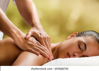 Close up of therapist doing neck massage on woman in spa against colorful green background.