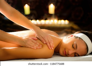 Close up of therapist massaging female spine in spa. Low key atmosphere with out of focus candles glowing in background.