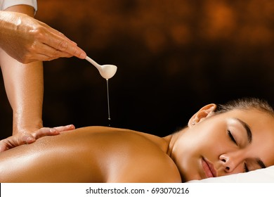 Close up of therapist pouring essential oil on female back in spa against dark brown background.