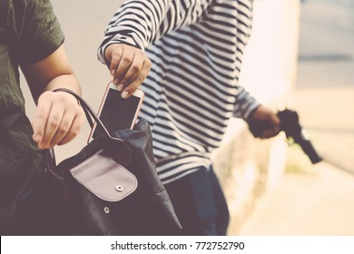 Close up of thief hand ,Thief stealing smart phone in handbag of woman ,Dangerous criminal of women in the city, Bad Man Concept.