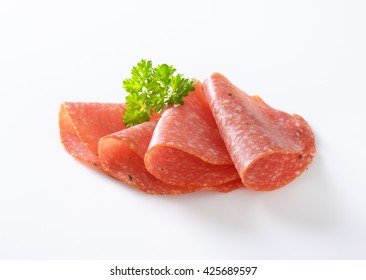 close up of thin slices of spicy salami folded on white background