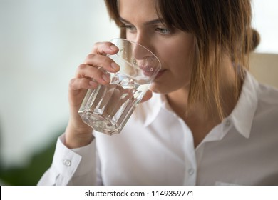 Close up of thirsty millennial female worker holding glass drinking pure mineral water in office, thoughtful dehydrated woman employee enjoying fresh aqua. Concept of healthy lifestyle