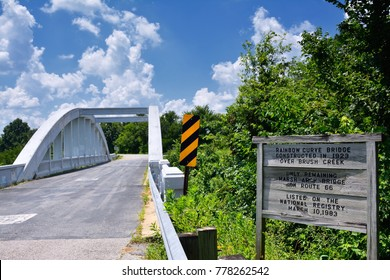 Close up of this Rainbow Curve Bridge Constructed in 1923 that is the only remaining Marsh Arch Bridge on Route 66. Route 66 signs are painted on the pavement.