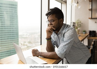 Close up thoughtful African American man wearing glasses looking at laptop screen, standing at wooden table, reading news, pensive businessman or student pondering online project strategy, brainstorm