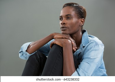 Close up of thoughtful of androgynous man in denim shirt posing against grey background