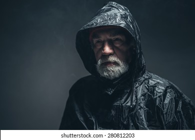 Close up Thoughtful Bearded Senior Man, Wearing Black Raincoat, Looking Into Distance and Thinking So Deep Against Black Background.