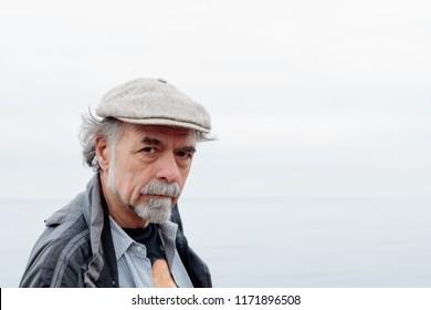 Close up of thoughtful, serious senior man with a gray beard wearing a tweed cap looking at camera