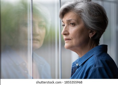 Close up thoughtful upset mature woman looking out window at home alone, sad senior grey haired female lost in thoughts, thinking about problem, nostalgia and melancholy, feeling lonely