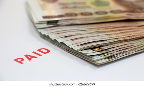 Close up thousand banknotes of Thailand with stamped PAID on white background.